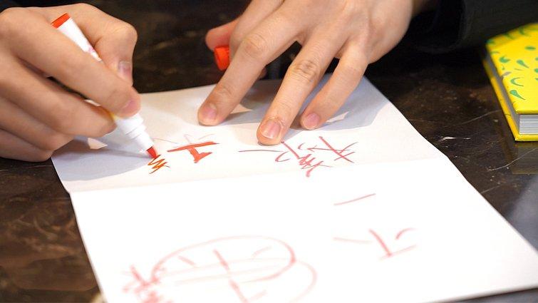 隨手拿起三種不同紅色的彩色筆,巧手一揮,原版的「不一樣」躍然紙上。